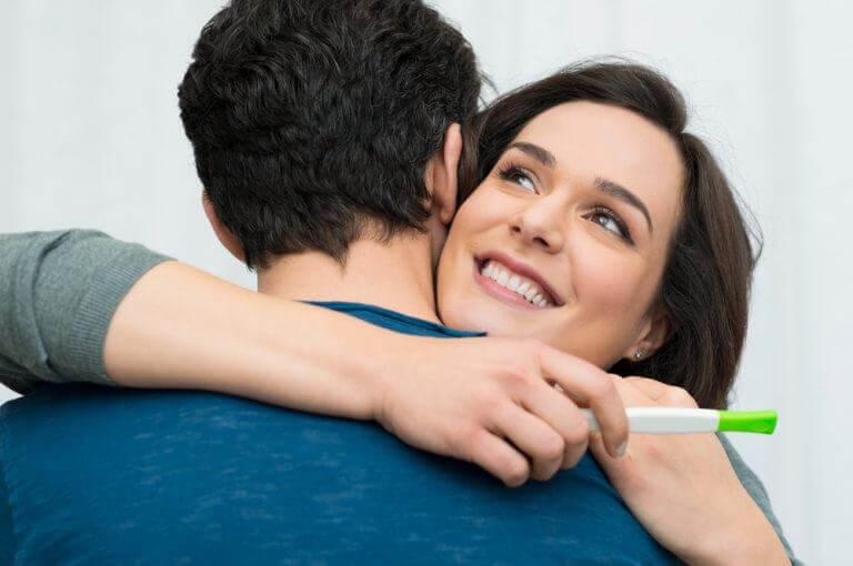 Vrouw die haar man knuffelt omdat ze zwanger is
