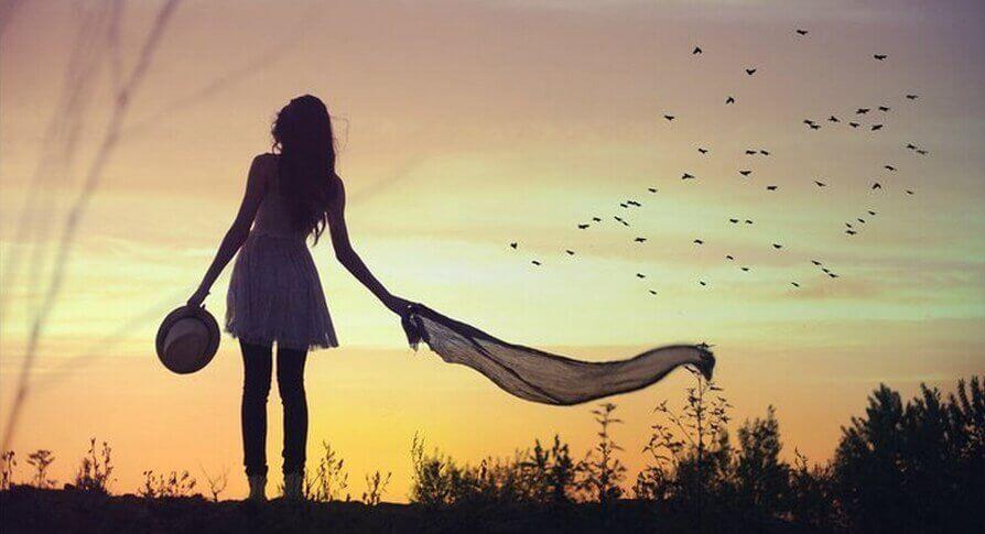 Een vrouw buiten met vogels in de lucht