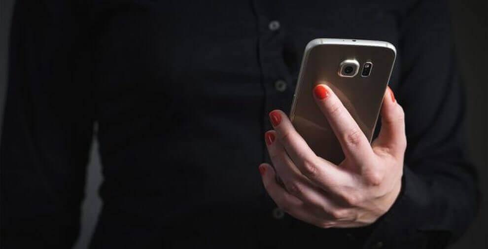 Vrouwenhand met rode nagels houdt haar smartphone vast
