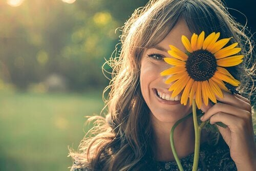 Lachende vrouw achter zonnebloem