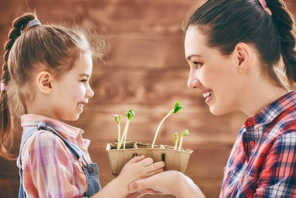 Supermoeder die plantjes plant met haar dochter
