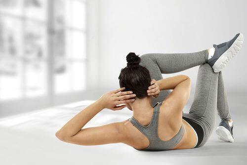 Vrouw in grijze sportkleding doet crunches