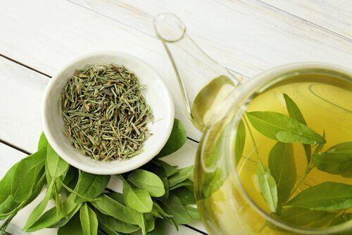 Kopje groene thee en losse thee blaadjes