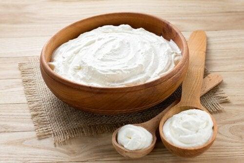 Houten kom en lepel met natuurlijke yoghurt