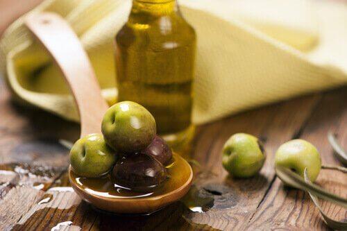 Olijven en olijfolie op een houten lepel