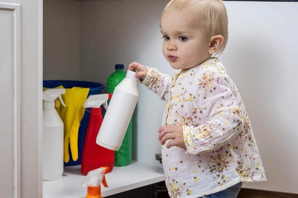 Peuter heeft een fles schoonmaakmiddel vast
