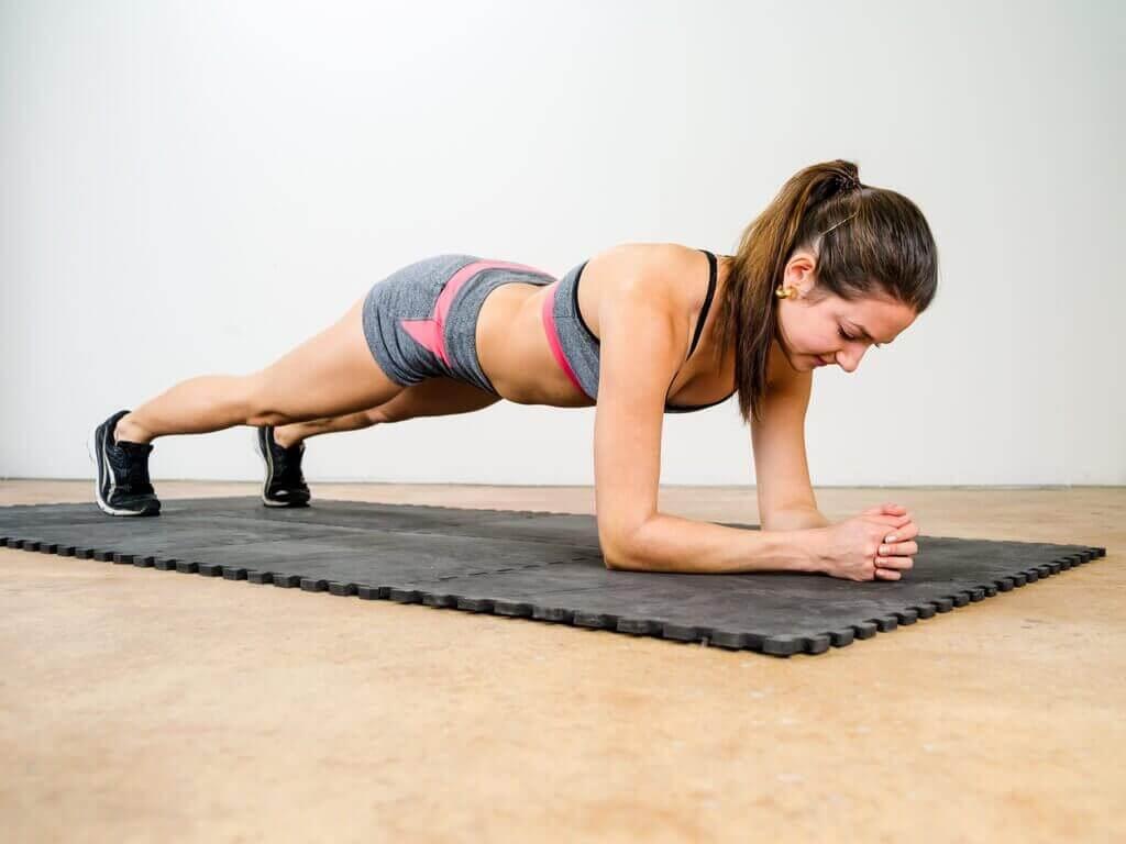 Vrouw in grijs en roze sportkleding doet de plank