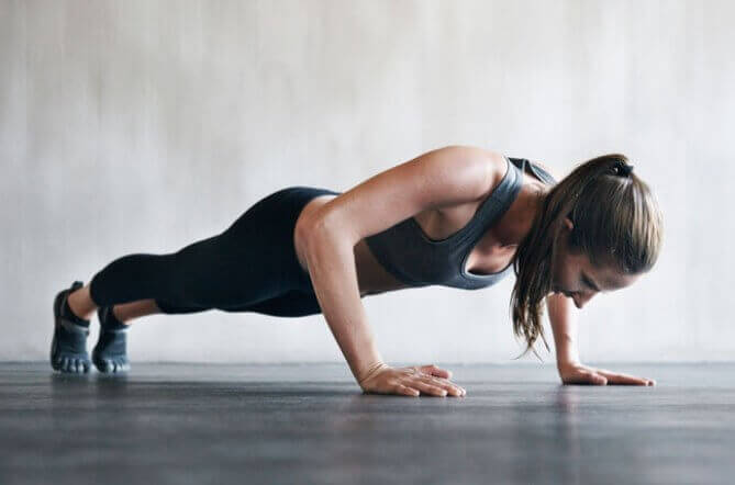 Vrouw in zwarte sportkleding doet push-ups