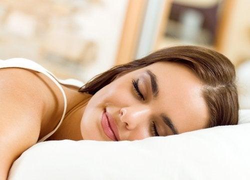 Vrouw slaapt op haar buik, met een glimlach op haar gezicht