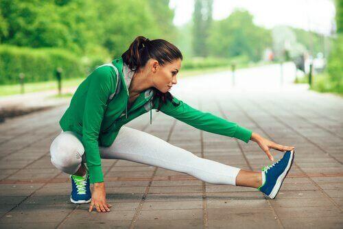 Vrouw in groen en wit sportpak is aan het rekken