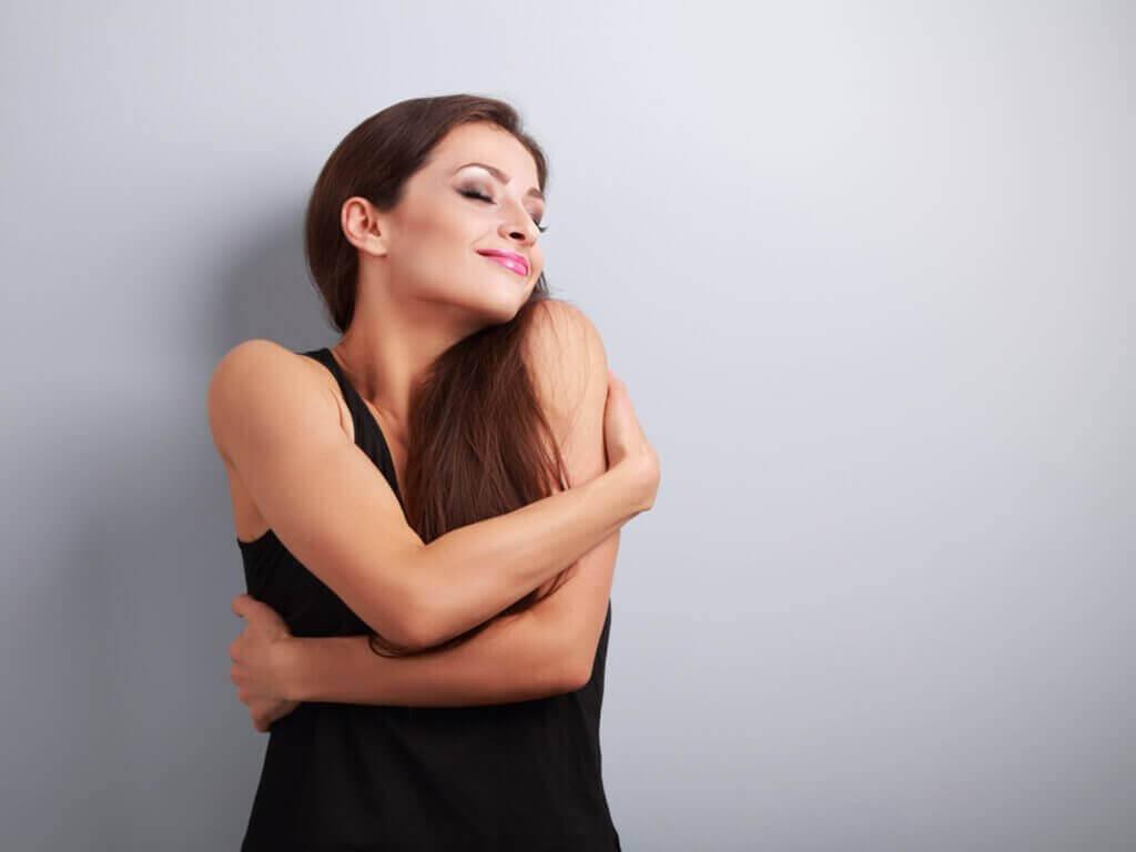 Vrouw omarmt zichzelf met een glimlach op haar gezicht