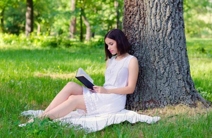 Vrouw zit onder een boom