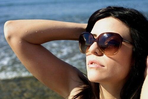 Vrouw in de zon op het strand met zonnebril