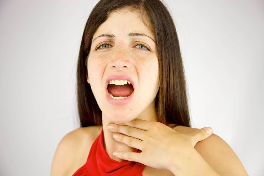 Vrouw raakt met hand pijnlijke keel aan