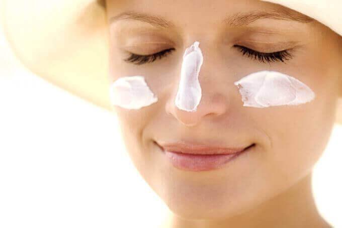 Vrouw met zonnehoed en zonnebrandcrème
