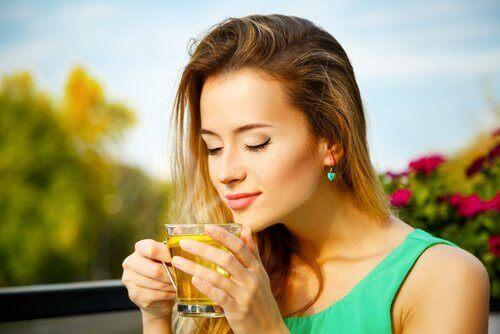 Blonde vrouw ruikt met gesloten ogen aan haar thee