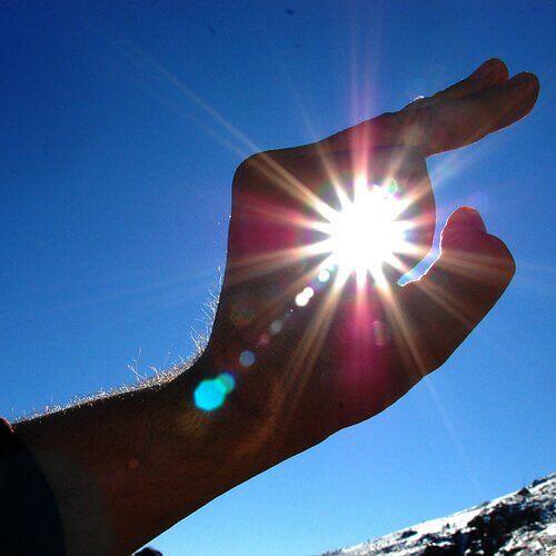 Tussen vingers door naar zonlicht kijken