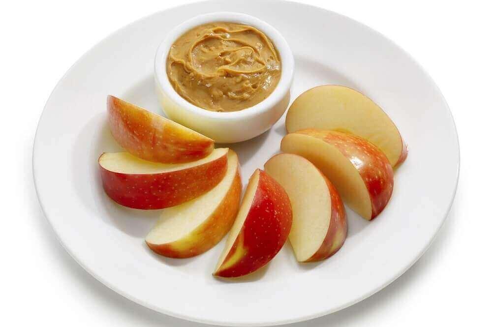 Bord met appelschijfjes en bakje pindakaas