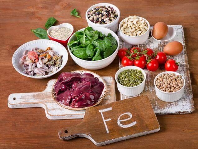 Gezonde voedingsmiddelen en een bordje met Fe de scheikundige benaming voor ijzer