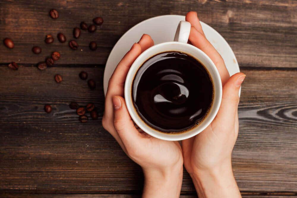 Handen houden kop koffie vast