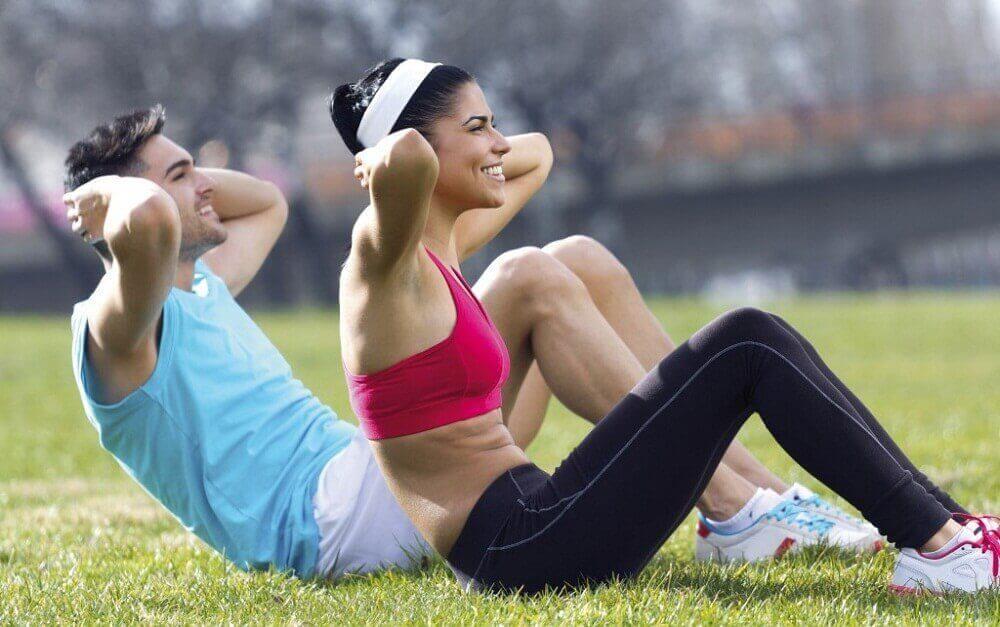 Man en vrouw in sportkleding doen sit-ups