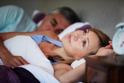 De man slaapt, de vrouw staart naar het plafond