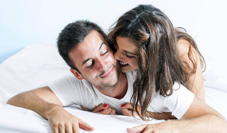 Man en vrouw stoeien op bed