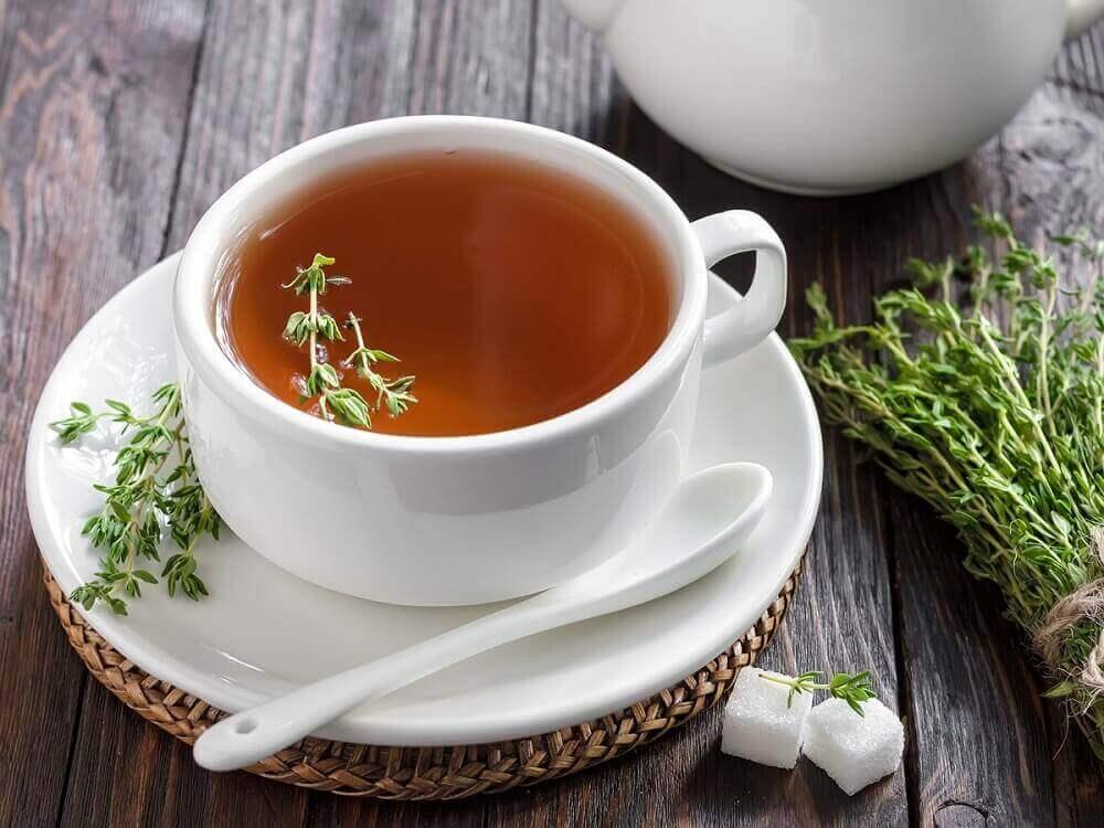 Wit kopje met een thee van tijm