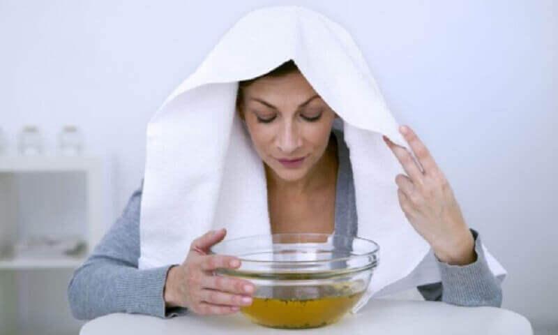 Vrouw met witte handdoek op haar hoofd om te stomen