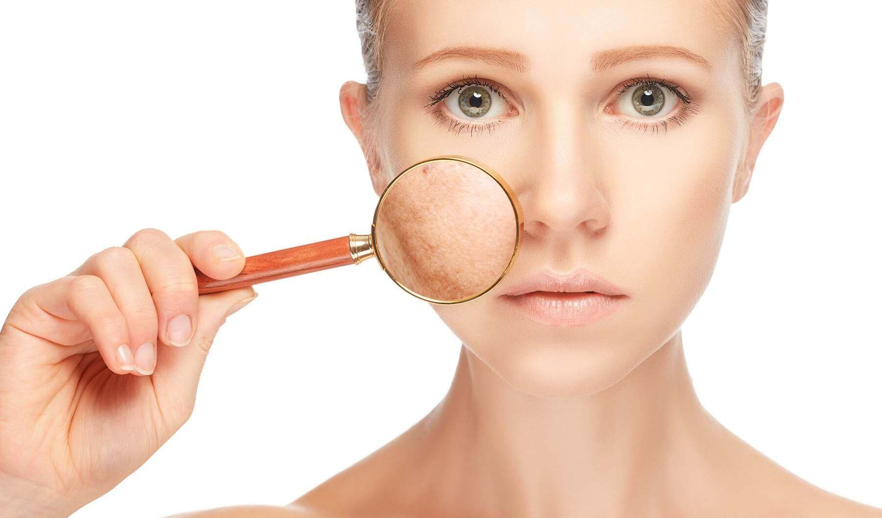 Vrouw houdt vergrootglas tegen haar huid