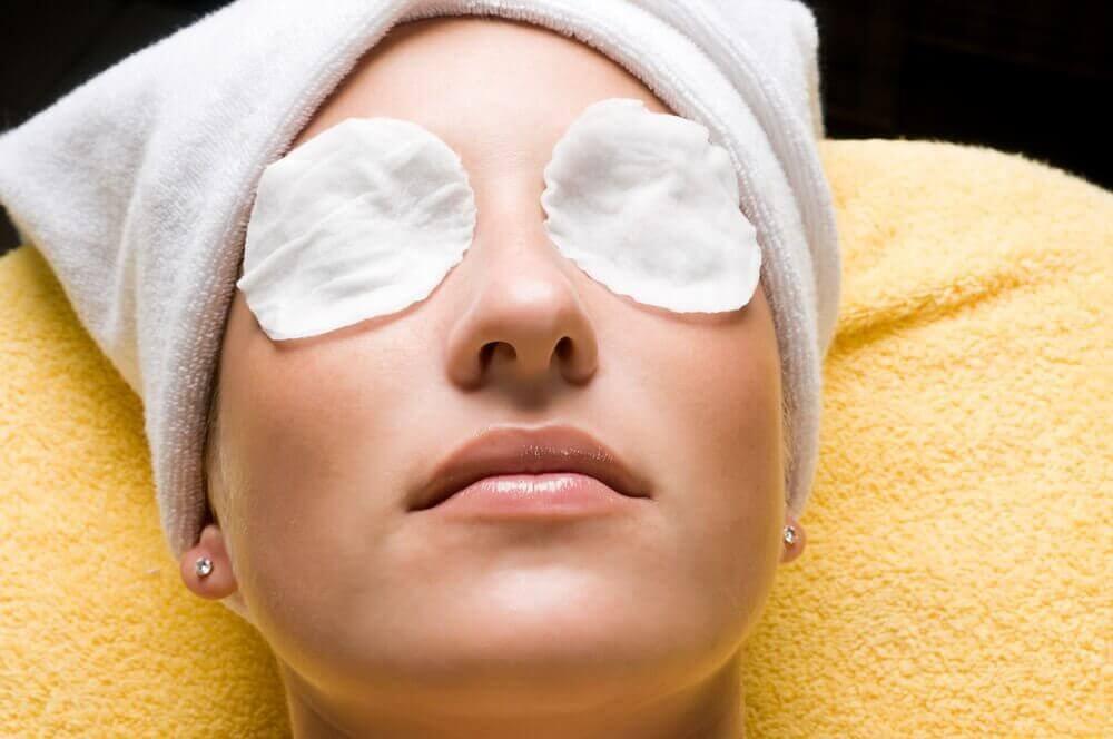 Vrouw ligt te ontspannen met wattenschijfjes op haar ogen