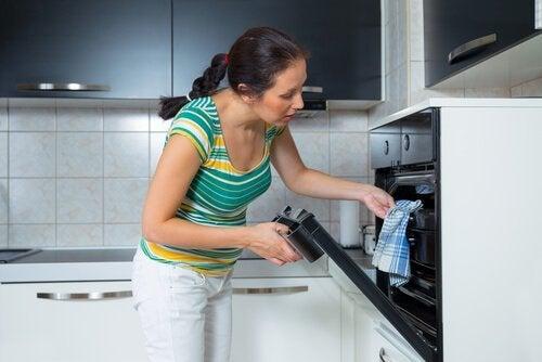 Vrouw die zelf zoet brood heeft gebakken en het zojuist uit de oven haalt