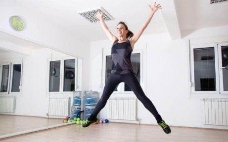 Vrouw die jumping jacks doet voor mooie benen