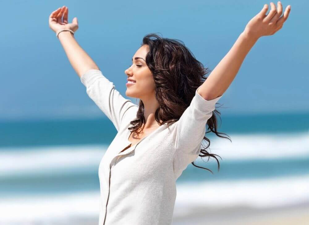 Vrouw staat met gespreide armen bij de zee