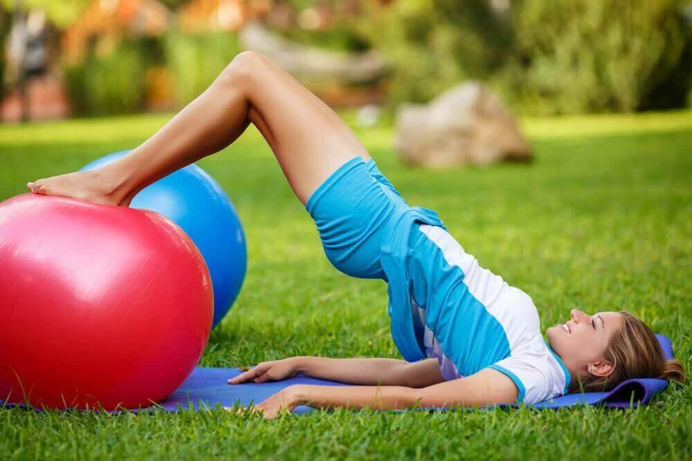 Vrouw doet de brug met een fitnessbal