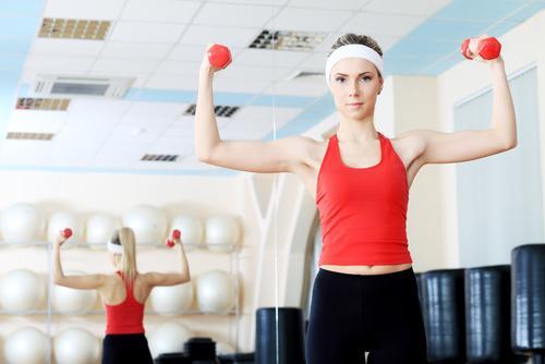 Vrouw doet oefeningen met dumbbells