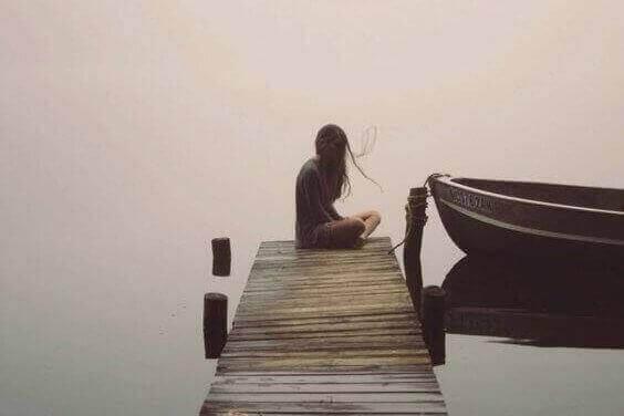 vrouw zit alleen op een steiger