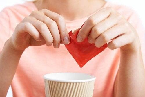 Vrouw opent zakje kunstmatige zoetstof