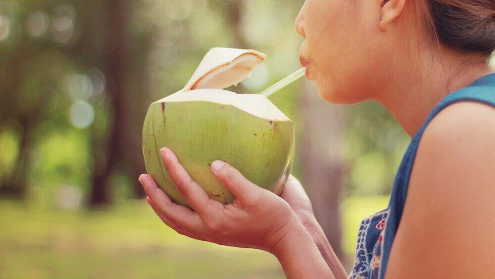 Vrouw drinkt uit kokosnoot