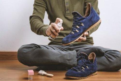 man gebruikt spray op suede schoenen