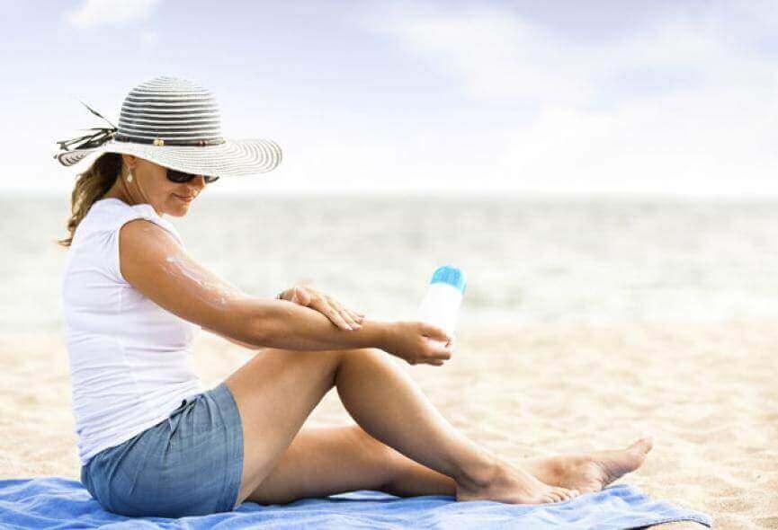 vrouw smeert zonnebrandmiddel op