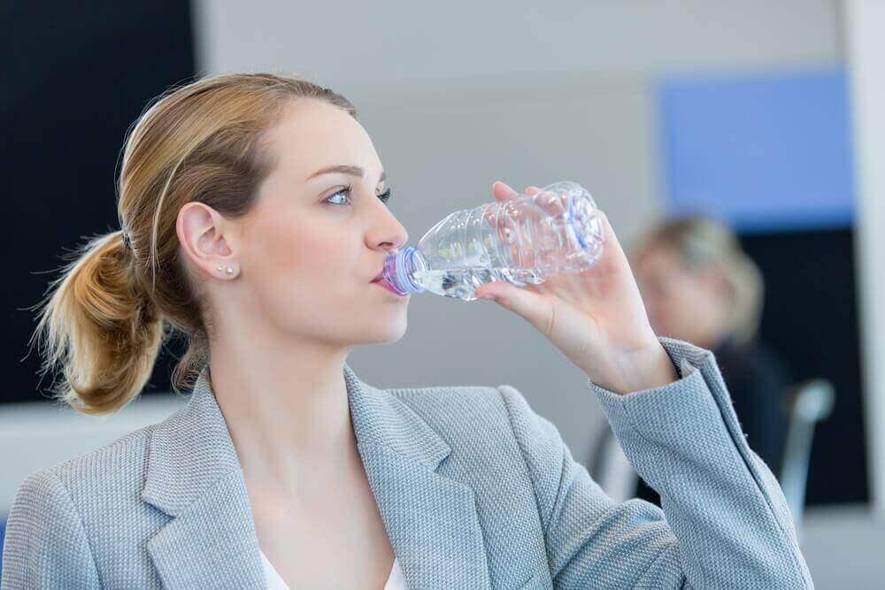 vrouw drinkt flesje water