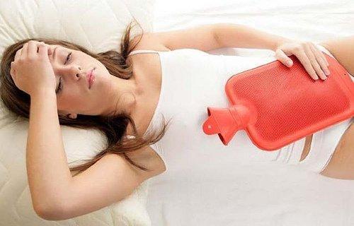 Vrouw met rode kruik op de buik