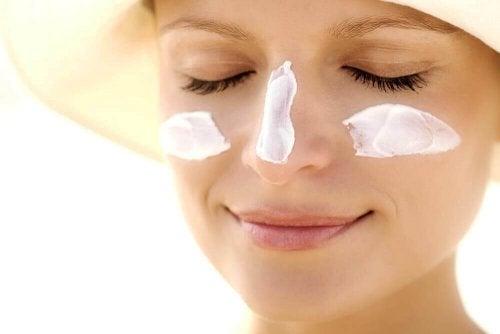 vrouw die lacht met zonnebrandcreme op haar gezicht