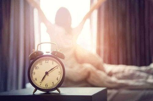 wekker met vrouw die zich uitrekt
