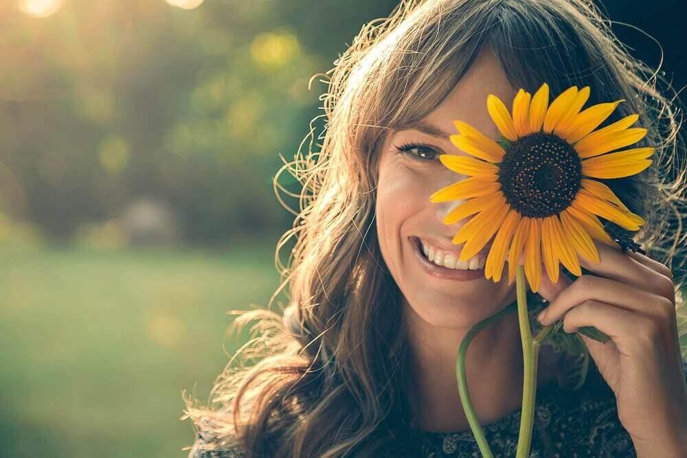 lachende vrouw met een zonnebloem