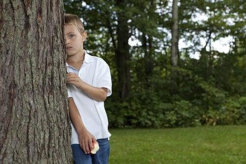 kind verstopt zich achter een boom