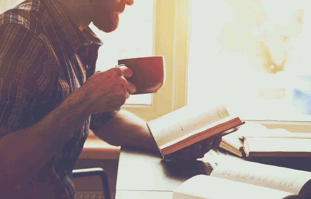 man met koffie leest een boek