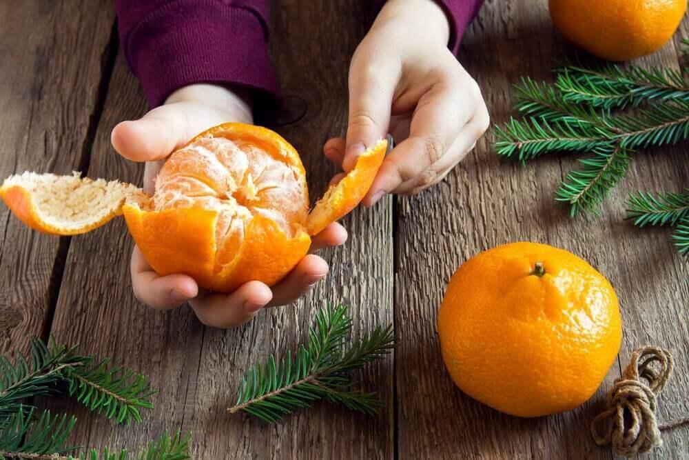 Handen die mandarijnen pellen