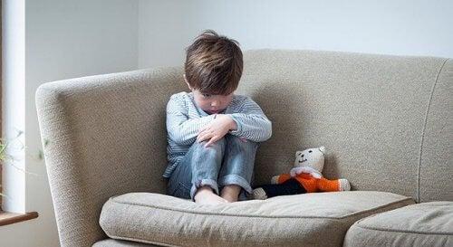 Teruggetrokken kind zit op de bank